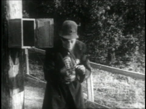 b/w 1916 keystone kop talking into old fashioned telephone at police phone box - 1916 stock videos & royalty-free footage
