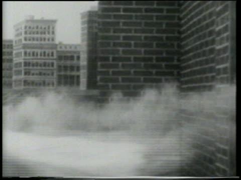 b/w 1915 keystone kop wearing nightgown holding on to smoking cannonball flying past brick building - スラップスティックコメディ点の映像素材/bロール