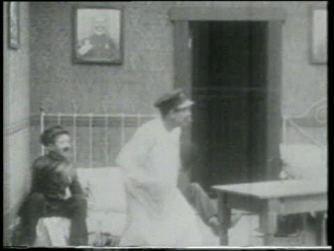 b/w 1915 keystone kop wearing nightgown in room catching smoking cannon ball + flying offscreen - スラップスティックコメディ点の映像素材/bロール