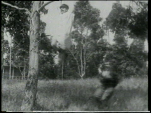 b/w 1915 keystone kop wearing nightgown swinging from tree branch kicking man running beneath him - 1915年点の映像素材/bロール