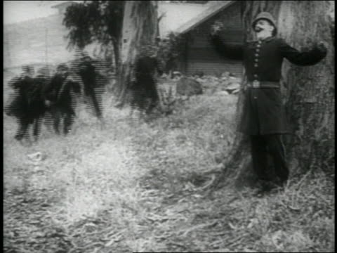 B/W 1914 Keystone Kops colliding into Kop stepping from behind tree / all Kops falling to ground