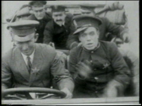 stockvideo's en b-roll-footage met b/w 1915 keystone kops crowded into car driving / feature - 1915