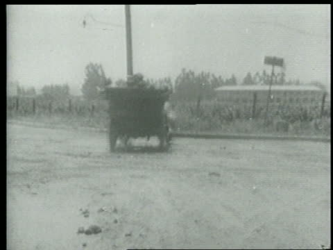 stockvideo's en b-roll-footage met b/w 1915 keystone kops driving car pulling away on dirt road / short - 1915