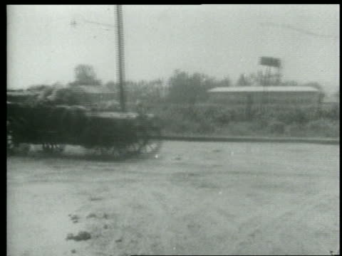 stockvideo's en b-roll-footage met b/w 1915 pan keystone kops driving car skidding on dirt road + coming to a stop / short - 1915