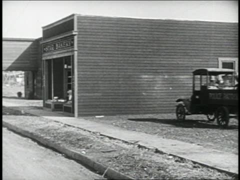 vidéos et rushes de b/w 1924 keystone kops driving police truck into side of building / feature - 1924