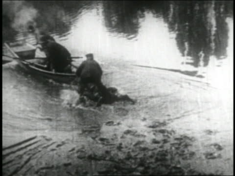 b/w 1916 keystone kops falling into shallow water + pushing boat into water / feature - 1916 stock videos & royalty-free footage