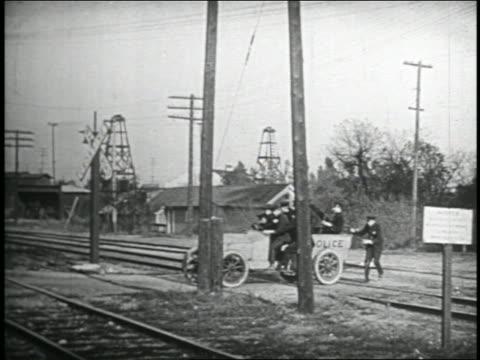 b/w 1935 keystone kops freeing police truck stuck on track narrowly avoiding oncoming train - 1935 stock videos & royalty-free footage