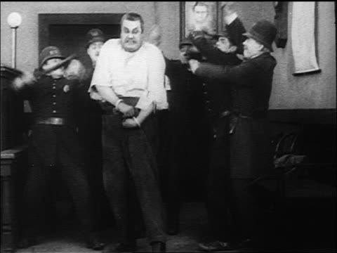 B/W 1917 Keystone Kops hitting large man (Eric Campbell) with nightsticks / man beating them all