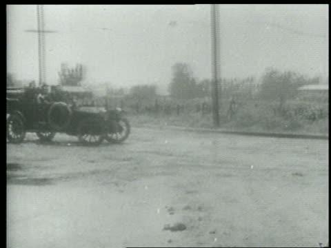 b/w 1915 keystone kops in car skidding + spinning to a stop on road / short - 1915年点の映像素材/bロール