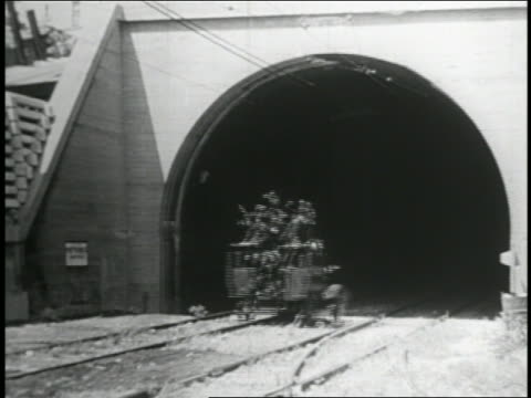 b/w 1935 keystone kops in police truck driving into + out of tunnel avoiding collisions with trolleys - 1935 stock videos & royalty-free footage