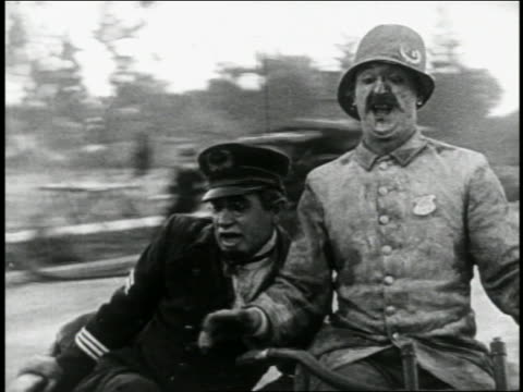 vidéos et rushes de b/w 1924 2 keystone kops on motorcycle with sidecar (1 is will rogers) spinning wildly on street - 1924