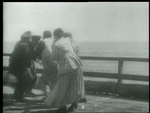 b/w 1915 keystone kops + others on edge of pier near water pulling rope / short - スラップスティックコメディ点の映像素材/bロール