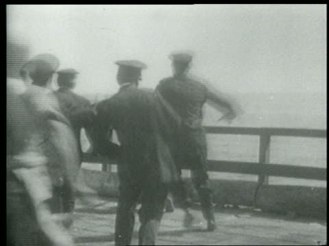 stockvideo's en b-roll-footage met b/w 1915 rear view keystone kops + others running up to railing at edge of pier + looking down - 1915