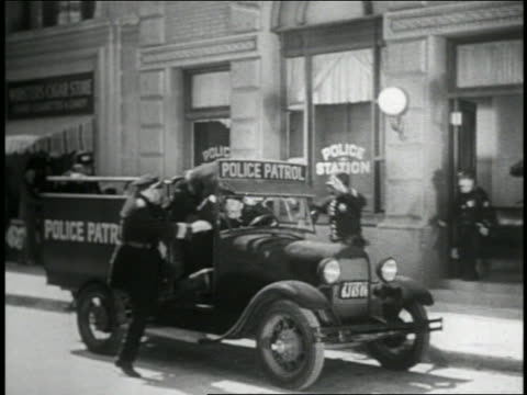 b/w 1935 keystone kops running + climbing into moving patrol truck / 2 miss truck + fall on street - 1935 stock videos & royalty-free footage