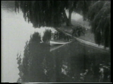 stockvideo's en b-roll-footage met b/w 1915 ha ws keystone kops running to edge of lake and boarding rowboat / feature - 1915