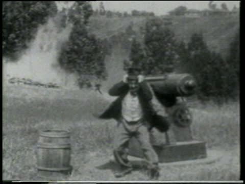 b/w 1915 keystone kops running toward man fretting near cannon on grassy hill in foreground / feature - 1915年点の映像素材/bロール
