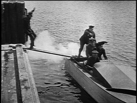 b/w 1916 keystone kops trying to jump into moving speedboat with some falling into water - falling water stock videos & royalty-free footage