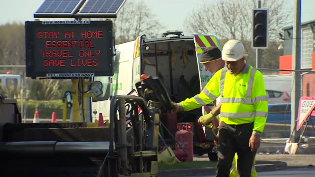 keyworkers fixing roads in liverpool sign urges people to stay at home during lockdown due to coronavirus pandemic - construction worker stock videos & royalty-free footage
