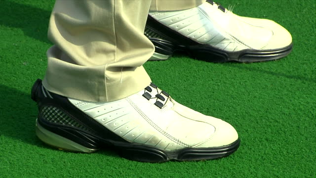 khaki pants hem draping onto golf shoes standing in set up stance on artificial turf w/ shadow of club by shoe shadow moving forward right foot... - golf shoe stock videos & royalty-free footage