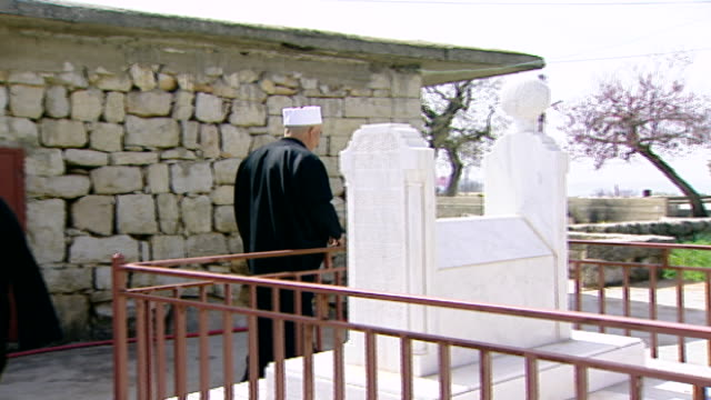 khalwat al-bayada. druze cleric sheikh fendi shouja looking at a marble tombstone with turban-shaped finial in the central sanctuary and theological... - turban stock videos & royalty-free footage