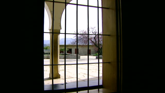 khalwat al-bayada. view of an arched loggia and courtyard through the bars of a window. khalwat al bayada is the central theological sanctuary of the... - theology stock videos & royalty-free footage