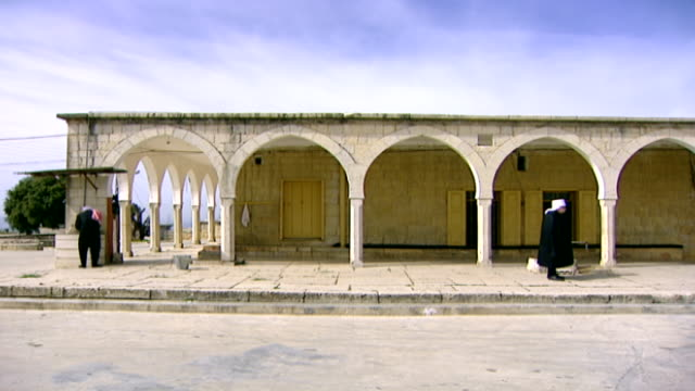 khalwat al-bayada. view of druze sheikhs, one performing his ablutions and one standing still, outside a prayer house in the central sanctuary of the... - theology stock videos & royalty-free footage