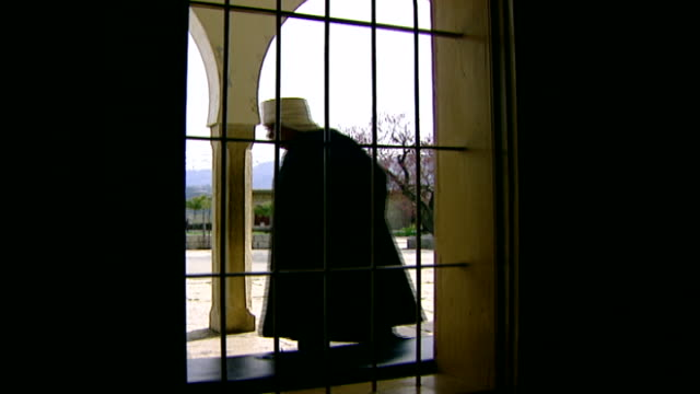 khalwat al-bayada. view onto a courtyard through a barred window. an old sheikh walks past the window. khalwat al bayada is the theological sanctuary... - theology stock videos & royalty-free footage