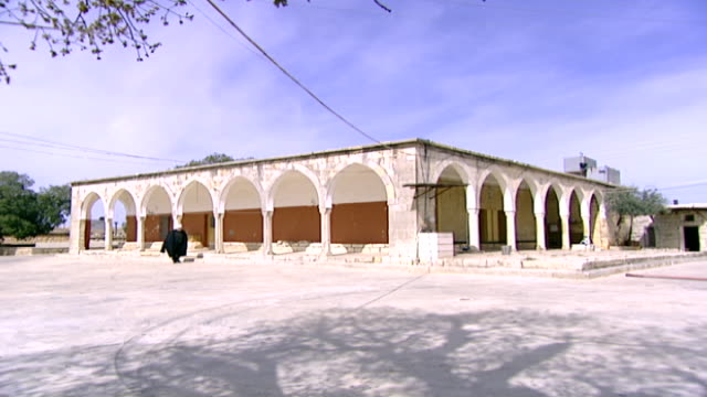 khalwat al-bayada. wide-shot of a druze sheikh walking past a prayer house in the central sanctuary and theological school of the druze in the chouf... - theology stock videos & royalty-free footage