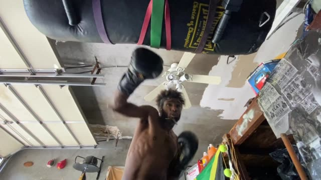 khamall dunkley hits the heavy bag in his training partner's garage on may 20, 2020 in freeport new york. khamall is an amateur boxer who fought in... - home economics点の映像素材/bロール