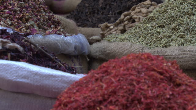 Khan al Khalili souk, Cairo, Egypt - close up spices with people moving past in foreground