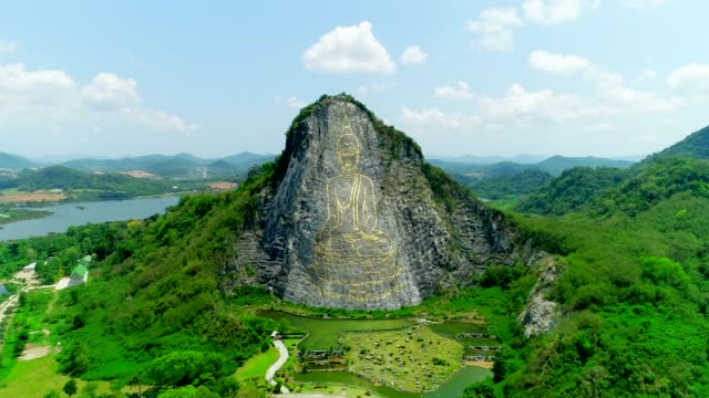 khao chee chan sculptural image , buddha mountain , is carved on the big mountain, drone fly in to the sky. - pattaya stock videos & royalty-free footage