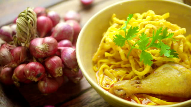 khao soi recipe, northern thai style curried noodle soup with chicken and group of red onion on a wooden table. - red onion stock videos & royalty-free footage