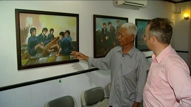 stockvideo's en b-roll-footage met khmer rouge prison chief found guilty of crimes against humanity int reporter looking at paintings with vann nath close shot painting of blindfolded... - bewegingsbeperkende middelen