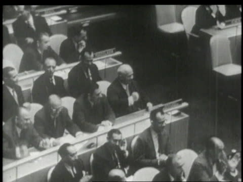 Khrushchev pounding his desk in contempt of Harold MacMillan speech while other United Nation members cheer / New York City New York United States