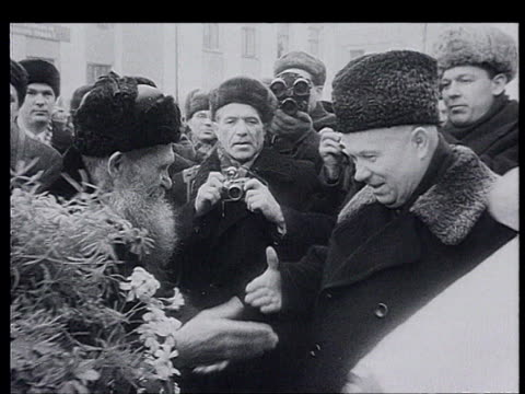 khrushchev visits the republics. novosibirsk : khrushchev deplane, welcomed with bread and salt, khrushchev kisses the bread. khrushchev's praise, vs... - オーバーコート点の映像素材/bロール
