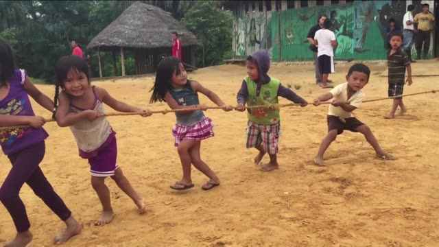 kichwa indian children in ecuador's autonomous indigenous amazonian region of sarayaku engage in a tug of rop contest in the village center. - エクアドル点の映像素材/bロール
