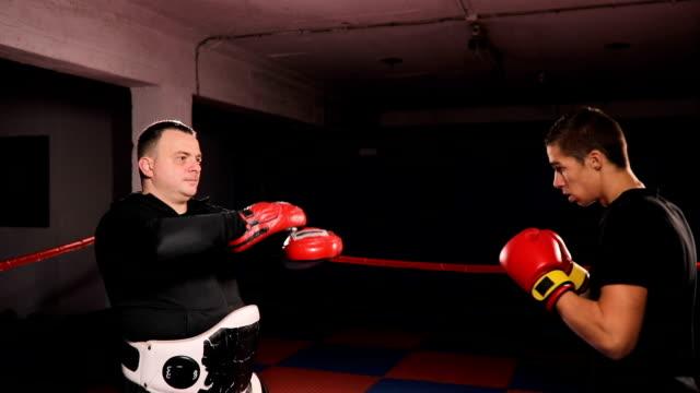 vídeos de stock, filmes e b-roll de lutador de caixa chute praticando com o treinador - posição de combate