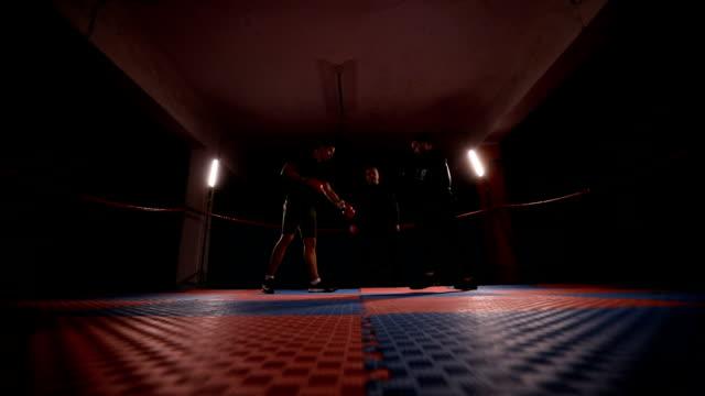 vídeos de stock, filmes e b-roll de kick boxers prática poupando no ringue de boxe - posição de combate