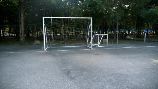 pov: kick fußball zum ziel am stadtpark. - asphalt stock-videos und b-roll-filmmaterial