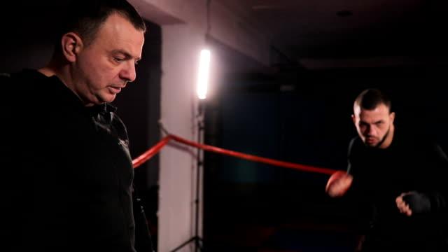 vídeos de stock, filmes e b-roll de kickboxers e treinador na prática - posição de combate