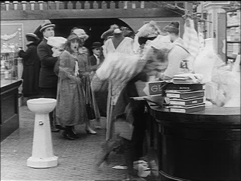 b/w 1916 kicked man (albert austin) stumbling across department store floor into display - コメディアン点の映像素材/bロール