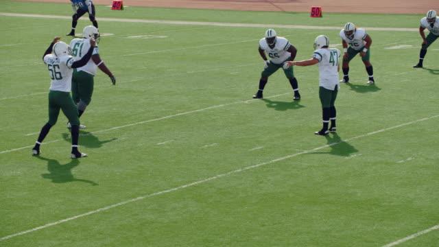 ws slo mo. kicker lines up shot, runs, and kicks off to receiving team at start of professional football game. - アメフトのユニフォーム点の映像素材/bロール