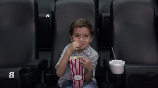 Kid at cinema watching a movie smiling