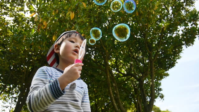 A kid blows bubble