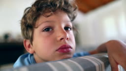 Kid boy at home seated in sofa feeling bored