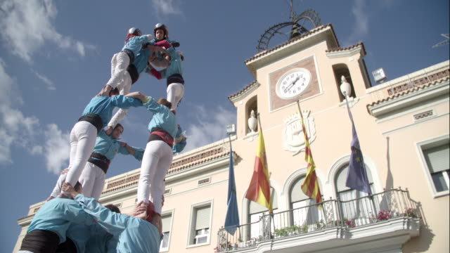 kid climbing to the top of castellers human pyramid - pyramid stock videos and b-roll footage