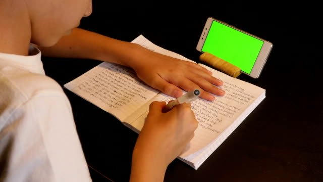 kid doing homework with a smartphone in slow motion - mobile app stock videos & royalty-free footage