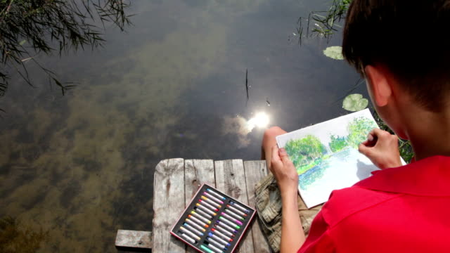 kid drawing a summer landscape with a forest lake - one teenage boy only stock videos & royalty-free footage