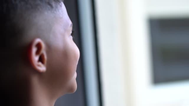 vídeos de stock, filmes e b-roll de garoto sonhar olhando pela janela - plano descrição geral
