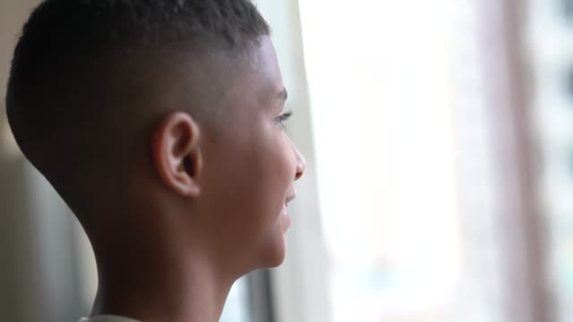 Kid dreaming looking through window